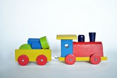 Wooden train, baby toy. Wooden train with locomotive and wagons, assembled with colored blocks,  on white background. part of a series Stock Photo