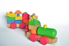 Wooden train, baby toy. Wooden train with locomotive and wagons, assembled with colored blocks,  on white background. part of a series Stock Photos