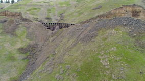 Wooden train trestle crosses a canyon in an Idaho forest. Half moon train trestle and Idaho forest stock video footage