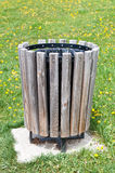 Wooden Trash Can in a Park. A wooden trash can sits on the dandelion filled grass in a local park Stock Photos