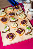 Wooden tray of appetizers on pallet coffee table at banquet with beetroot, citron, green herbs and hummus. Stock Images