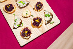 Wooden tray of appetizers on pallet coffee table at banquet with beetroot, citron, green herbs and hummus. Royalty Free Stock Photo