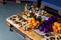 Wooden tray of appetizers on pallet coffee table Stock Photography