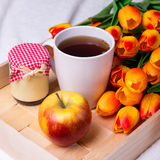 Wooden tray with cup of tea, jar of jam or honey, apple and flow Royalty Free Stock Photo