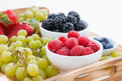 Wooden tray with fresh berries and grapes, close-up Stock Photos