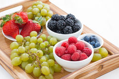 Wooden tray with fresh berries and grapes Stock Image