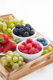 Wooden tray with fresh berries and grapes, vertical Royalty Free Stock Photos