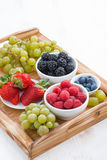 Wooden tray with fresh berries and grapes, vertical, top view Royalty Free Stock Photos