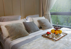 Wooden tray with fresh fruits on bed Stock Photo