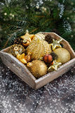 Wooden tray with golden Christmas decorations on table Royalty Free Stock Image