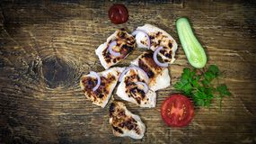 On a wooden tray grilled chicken with vegetables Stock Photo