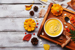 Wooden tray with hot autumn pumpkin soup decorated sesame seeds and thyme in white bowl on rustic vintage table top view. Royalty Free Stock Photography