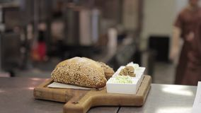 On a wooden tray lie buns with sesame and plates with condiments. In a large restaurant kitchen is ready to take out a plate with bread and different sauces stock video