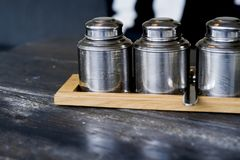 Wooden tray with metal tea jars on table. royalty free stock photo