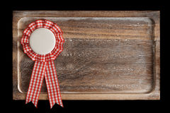 Wooden tray with round ribbon seal or badge,. On black, copy space royalty free stock images