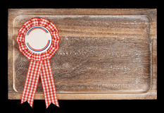 Wooden tray with round ribbon seal or badge, isolated. On black background royalty free stock image