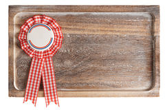 Wooden tray with round ribbon seal, isolated on white. Wooden tray with round ribbon seal or badge, isolated on white without shadows royalty free stock photo