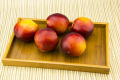 In the wooden tray, some red nectarine,. Beautiful color, rich nutrition Royalty Free Stock Images
