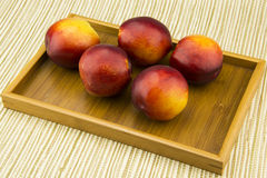 In the wooden tray, some red nectarine, Royalty Free Stock Images