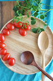 Wooden tray and spoon with fresh tomato Royalty Free Stock Images