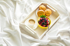 Wooden tray with tasty breakfast on bed. Espresso, banana muffins, cottage cheese with blueberry and raspberry Stock Photo