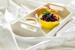 Wooden tray with tasty breakfast on bed. Espresso, banana muffins, cottage cheese with blueberry and raspberry Royalty Free Stock Images