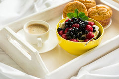 Wooden tray with tasty breakfast on bed. Espresso, banana muffins, cottage cheese with blueberry and raspberry Stock Images