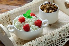 Wooden tray with tasty breakfast : cottage cheese with fresh raspberries and granola. Homemade breakfast: cottage cheese with fresh raspberries and granola. In Royalty Free Stock Photography