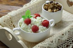 Wooden tray with tasty breakfast : cottage cheese with fresh raspberries and granola. Homemade breakfast: cottage cheese with fresh raspberries and granola. In Stock Image