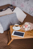 Wooden tray with tea, flowers and e-book standing on a bed Royalty Free Stock Images