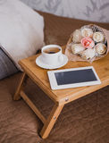 Wooden tray with tea, flowers and e-book standing on a bed Stock Photo