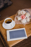 Wooden tray with tea, flowers and e-book standing on a bed Stock Photography