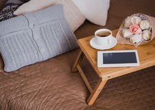 Wooden tray with tea, flowers and e-book standing on a bed Stock Images