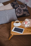 Wooden tray with tea, flowers and e-book standing on a bed Royalty Free Stock Image