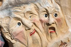 Wooden Tree Sculpture: Close-up of Faces Carved in Wood, Handmade.  Royalty Free Stock Image