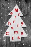 Wooden tree with text: Merry Christmas in red and grey colors. Stock Image