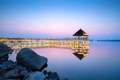 Wooden trestle bridge. Tranquil lake and wooden trestle, evening landscape Stock Images