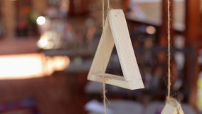 Wooden triangle on a rope in the wedding decor. stock video footage