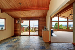 Wooden trim home with open floor plan. Wooden cabinet with granite counter top. Also tile floor and exit to balcony with perfect water view. Northwest, USA stock photography