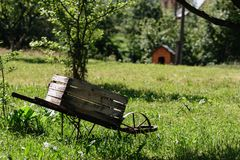 Wooden trolley in the garden. A trolley with a wooden box in the garden against the background of a dog booth royalty free stock images