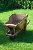 Wooden trolley on green grass in the garden Stock Images