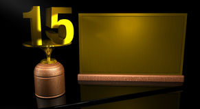 Wooden trophy with number 15 in gold and golden plate with space to write on mirror table in black background Royalty Free Stock Photo