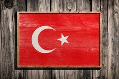 Wooden Turkey flag. 3d rendering of Turkey flag on a wooden frame over a planks wall stock image