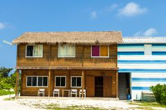 Wooden two-storey guest house, Kaafu Atoll, Kuda Huraa Island, Maldive. Wooden guest house under the roof of a dry palm leaf on a blue sky background, Kaafu Stock Image