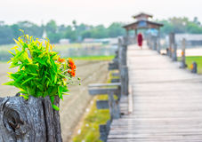 Wooden Ubein footbridge in Mandalay Myanmar. With flowers in foreground and monk in background Stock Photography