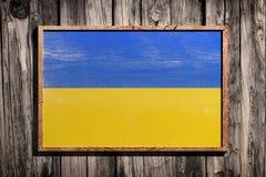 Wooden Ukraine flag. 3d rendering of Ukraine flag on a wooden frame over a planks wall stock images