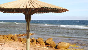 Wooden umbrella on a deserted beach. Dahab Egypt stock footage