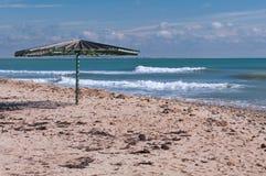 Wooden umbrella on empty beach Stock Image