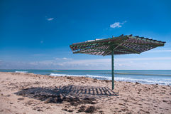 Wooden umbrella on empty beach. Canopy in the form of umbrella on empty beach Royalty Free Stock Photos