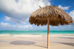 Wooden umbrella on empty sandy beach Stock Images